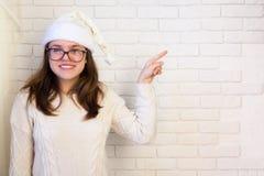 圣诞节盖帽的一个女孩指向白色墙壁 免版税库存图片
