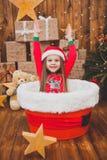 圣诞节睡衣和圣诞老人帽子的小女孩在圣诞节背景中 免版税库存照片