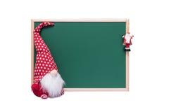 圣诞节矮子和圣诞老人装饰品在空的绿色查家旁边 免版税库存照片