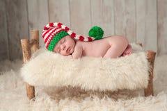 戴圣诞节矮子帽子的新出生的男婴 免版税图库摄影