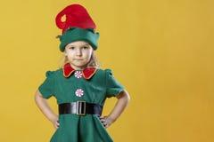 圣诞节矮子的服装的一个小女孩休息她的在她的臀部的手 在文本的空白的地方附近,复制空间 免版税库存图片