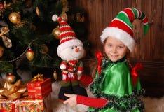 圣诞节矮子的衣服的小女孩与礼物的 免版税图库摄影
