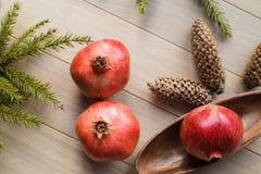 圣诞节石榴石果子,云杉的树枝,在织地不很细背景的大爆沸 免版税库存照片