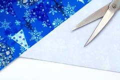 圣诞节礼品包装材料与五颜六色的纸、丝带弓、剪刀和磁带的党时间在深蓝蓝色破旧的别致的木委员会Backgro 图库摄影