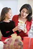 圣诞节礼品女孩惊奇她的母亲 库存图片