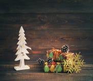 圣诞节礼品隔离白色 在五颜六色的纸的欢乐箱子与在木背景的一棵木装饰新年树 库存图片