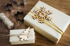 圣诞节礼品隔离白色 用木雪花、圣诞树和黄麻装饰的欢乐箱子顶视图在木表上 免版税库存照片