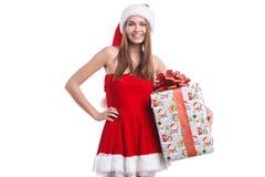 圣诞节礼服和圣诞老人帽子的深色的女孩拿着一个礼物盒 背景查出的白色 库存图片