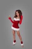圣诞节礼服的美丽的妇女在充分的高度的灰色背景与香槟和看照相机玻璃  图库摄影