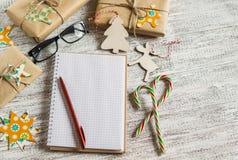 圣诞节礼物、圣诞节装饰品、糖果和一个开放空白的笔记本 免版税图库摄影