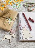 圣诞节礼物、圣诞节装饰品、糖果和一个开放空白的笔记本 免版税库存图片