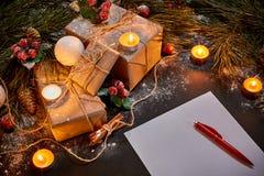 圣诞节礼物、灼烧的说谎在黑背景顶视图的绿色云杉的分支附近的蜡烛和笔记本 空间为 库存图片