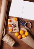 圣诞节礼物包裹在卡拉服特样式的 蜜桔,黄麻,纸卷,剪刀,刻痕 与自由地方的书文本的 免版税图库摄影