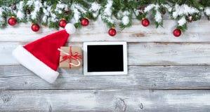 圣诞节礼物和技术背景在土气白色木头 库存图片