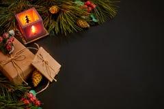 圣诞节礼物和红色烛台在绿色云杉的分支附近在黑背景 抽象空白背景圣诞节黑暗的装饰设计模式红色的星形 顶视图 库存图片
