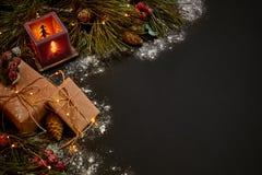 圣诞节礼物和红色烛台在绿色云杉的分支附近在黑背景 抽象空白背景圣诞节黑暗的装饰设计模式红色的星形 顶视图 免版税库存照片