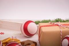 圣诞节礼物和装饰品与杉树在木backgrou 免版税库存照片