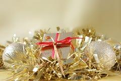 圣诞节礼物和装饰在金闪亮金属片 免版税图库摄影