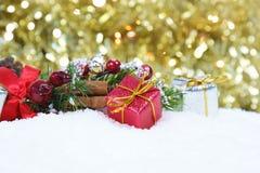 圣诞节礼物和装饰在雪反对金bokeh ligh 免版税库存照片