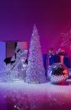 圣诞节礼物和装饰在紫色背景 免版税库存照片