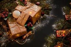 圣诞节礼物和诗歌选在绿色云杉的分支附近在黑背景 抽象空白背景圣诞节黑暗的装饰设计模式红色的星形 顶视图 免版税库存照片