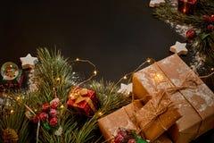 圣诞节礼物和诗歌选在绿色云杉的分支附近在黑背景 抽象空白背景圣诞节黑暗的装饰设计模式红色的星形 顶视图 免版税库存图片