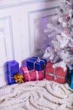 圣诞节礼物在一个现代设置的一棵圣诞树下 免版税库存图片