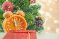圣诞节礼物庆祝时间橙色时钟和圣诞树 免版税库存照片