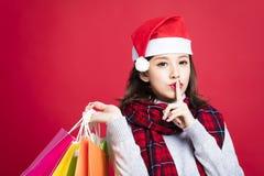 圣诞节礼物的妇女购物与秘密姿态 免版税库存图片