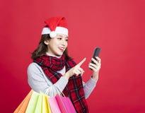 圣诞节礼物的妇女购物由巧妙的电话 免版税库存图片