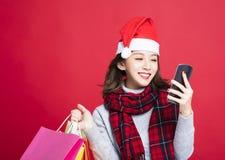 圣诞节礼物的妇女购物由巧妙的电话 免版税图库摄影