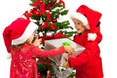 给圣诞节礼物的男孩女孩 免版税库存图片
