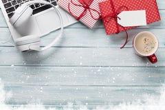 圣诞节礼物盒、个人计算机和咖啡杯在木头 免版税图库摄影