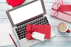 圣诞节礼物盒、个人计算机和咖啡杯在木头 免版税库存图片