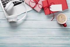 圣诞节礼物盒、个人计算机和咖啡杯在木头 库存照片