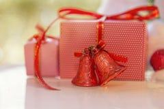 圣诞节礼物盒、红色门铃和被弄脏的杉树反对 免版税库存图片