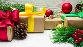 圣诞节礼物盒和分支圣诞树和球玩具和锥体在白色木葡萄酒背景 库存图片