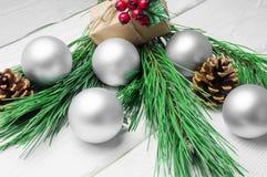 圣诞节礼物盒和分支圣诞树和银球和锥体在白色木土气背景 免版税库存图片