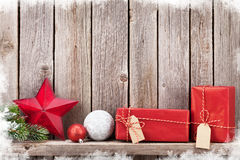 圣诞节礼物盒和装饰在木墙壁前面 免版税库存图片