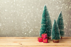 圣诞节礼物盒在木桌上的杉树下在bokeh背景 免版税库存照片