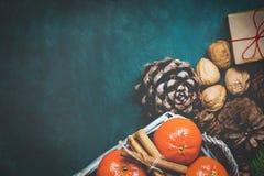 圣诞节礼物盒有红色麻线蜜桔肉桂条杉树分支杉木锥体核桃深蓝背景 免版税库存图片