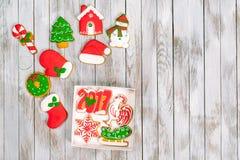 圣诞节礼物盒用在白色木后面的姜饼曲奇饼 免版税库存图片