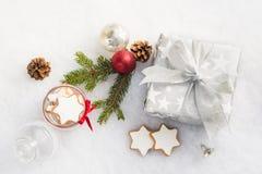 圣诞节礼物盒的顶视图在银色包装纸的在白色蓬松背景 充分瓶子星曲奇饼和christma 库存图片