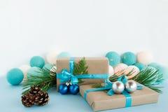 圣诞节礼物盒被包裹工艺纸,蓝色和白色丝带,装饰冷杉分支、圣诞节球和杉木锥体 库存图片
