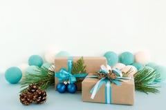 圣诞节礼物盒被包裹工艺纸,蓝色和白色丝带,装饰冷杉分支、杉木锥体和圣诞节球 库存图片