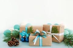 圣诞节礼物盒被包裹工艺纸,蓝色和白色丝带,装饰冷杉分支、杉木锥体和圣诞节球 免版税库存图片