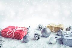 圣诞节礼物盒,当前与在雪背景的装饰品 免版税图库摄影