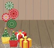 圣诞节礼物盒,杯形蛋糕,在地板上的球 图库摄影