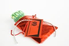 圣诞节礼物,出现日历,与金钱的小袋子 免版税库存照片