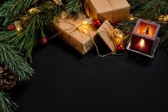 圣诞节礼物,圣诞树,蜡烛,上色了装饰,星,在黑背景的球 免版税库存照片